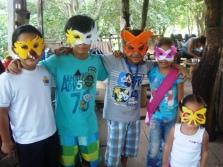 Niños del Fisher Kids Bilingual School con máscaras hechas con botellas plásticas
