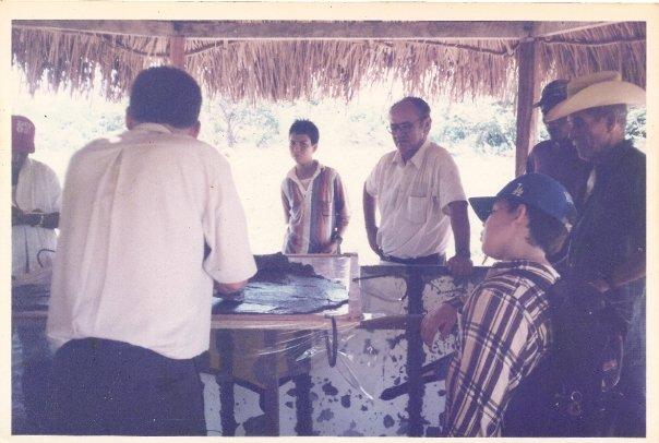 Foto antigua de un grupo de hombres bajo un kiosko de palma