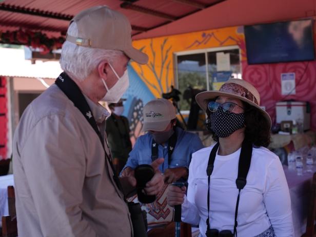 Hombre y mujer conversando con tapabocas.