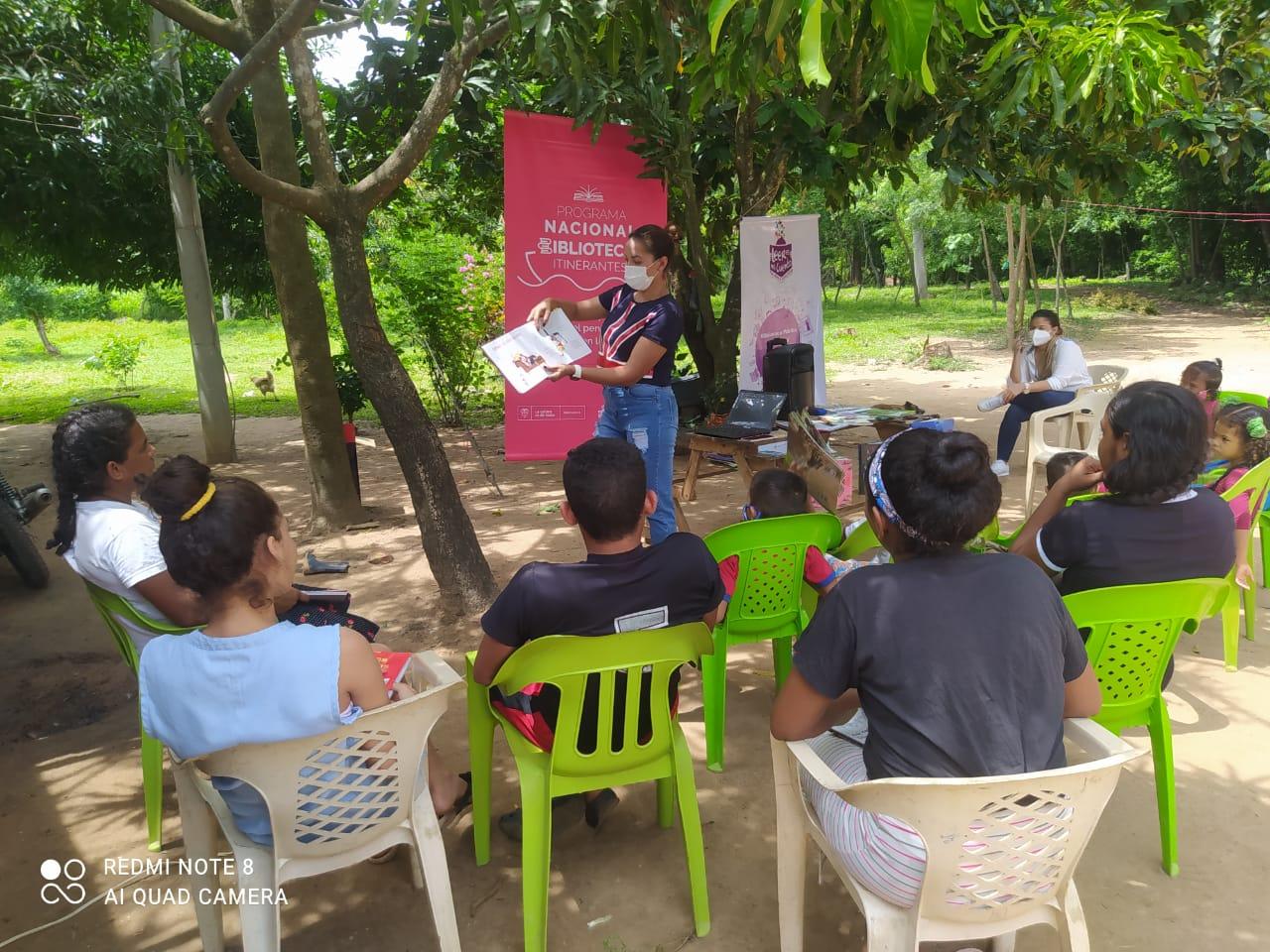 Niños reunidos durante una actividad cultural bajo los árboles.